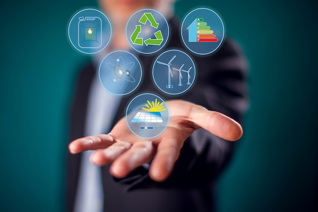 Бизнесмен в костюме с виртуальными кнопками экономии энергии. концепция альтернативной энергетики и защиты окружающей среды