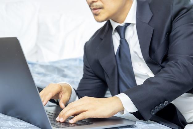 Бизнесмен в костюме работая на компьтер-книжке пока сидящ на кровати, работа от домашней концепции.