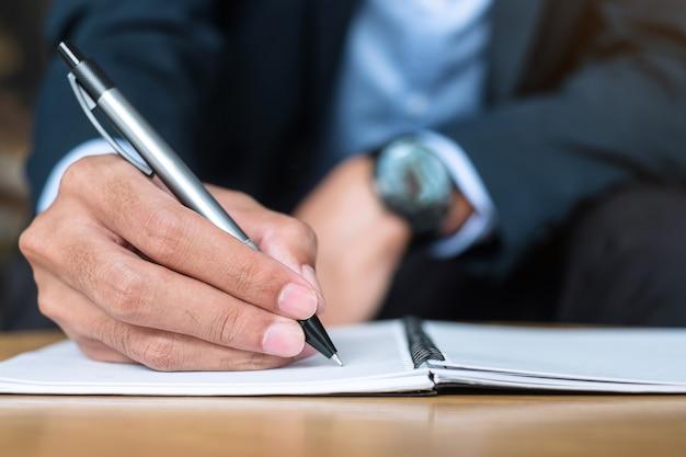 사무실이나 카페, 종이 보고서에 서명으로 펜을 들고 남자의 손에 노트북에 뭔가 쓰는 소송에서 사업가. 비즈니스 개념