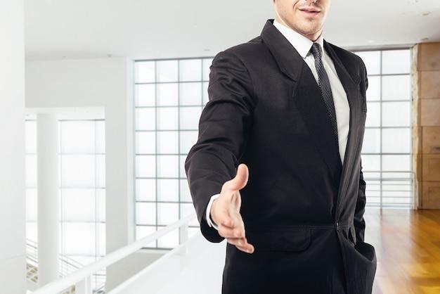 ネクタイと黒のスーツを着たビジネスマンが手を伸ばし、ガラスの壁のあるビジネスセンター