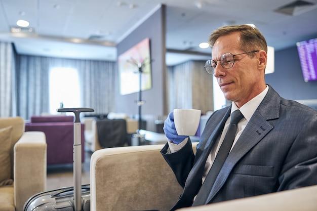 ネクタイと眼鏡のビジネスマンは、検疫中に出発を待っている間、肘掛け椅子に座ってコーヒーを飲んでいます