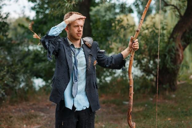 無人島で弓で引き裂かれたスーツ狩りのビジネスマン。