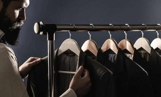 조끼를 입은 사업가, 가게에서 한 벌의 행. 쇼룸에서 옷을 입어보고 포즈를 취하고 있는 모습입니다. 천 재킷에 세련 된 남자입니다.