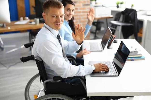 車椅子のビジネスマンとテーブルの実業家は笑顔で挨拶で手を上げています
