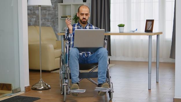 自宅で仕事をしながらビデオ通話中に手を振っている車椅子のビジネスマン。