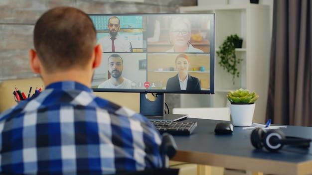 Бизнесмен в инвалидной коляске, размахивая во время видеозвонка с деловыми партнерами.