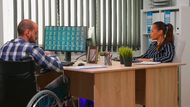 회사 사무실에서 일하는 휠체어 사업가가 그래프를 분석하는 문서를 변경합니다. 현대 회사의 직원들은 컴퓨터 키보드로 입력하고 데스크톱 확인 클라이언트 목록을 가리키고 있습니다.