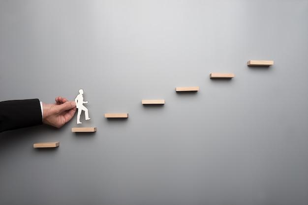 Бизнесмен в белой рубашке, строя диаграмму или лестницу успеха на серой стене.