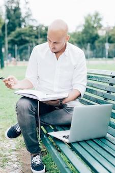 Бизнесмен в белой рубашке, работа с ноутбуком, сидя на скамейке в парке