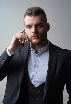 電話モービルで仕事をしているビジネスマン。クラシックなスーツ。男のスーツのファッション。会議の電話。