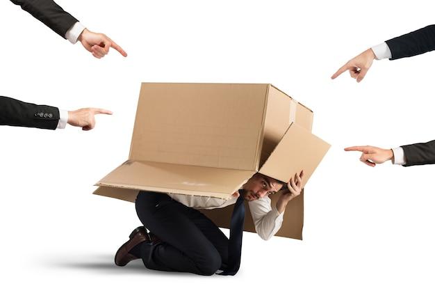 段ボールに隠れている同僚によって示されるビジネスマン