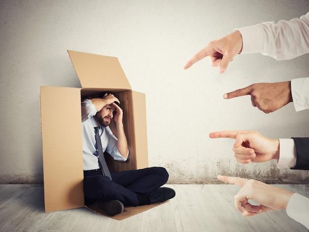 Бизнесмен, на которого указывают коллеги, прячущиеся в картоне