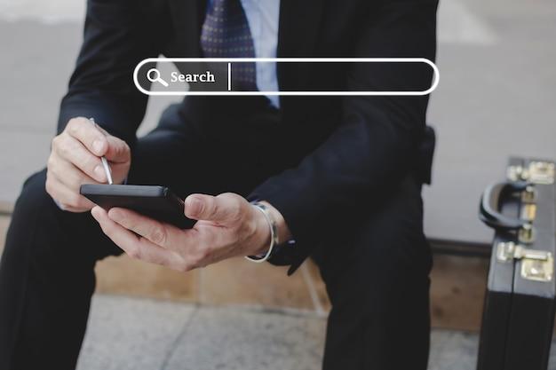 検索バーのグラフィック、検索ウェブ、ソーシャルネットワーク、インターネットオンライン、求人検索エンジン、ビジネスファイナンス、デジタル技術の概念を備えた携帯電話でスタイラスペンを使用してスーツを着たビジネスマンの投資家