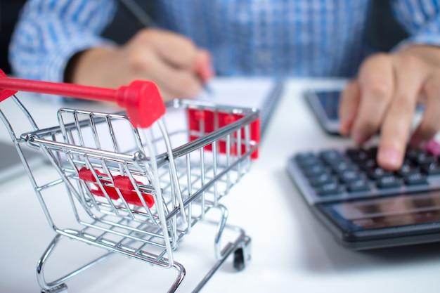 Бизнесмен вычисляет цену. для покупок в интернете. Premium Фотографии