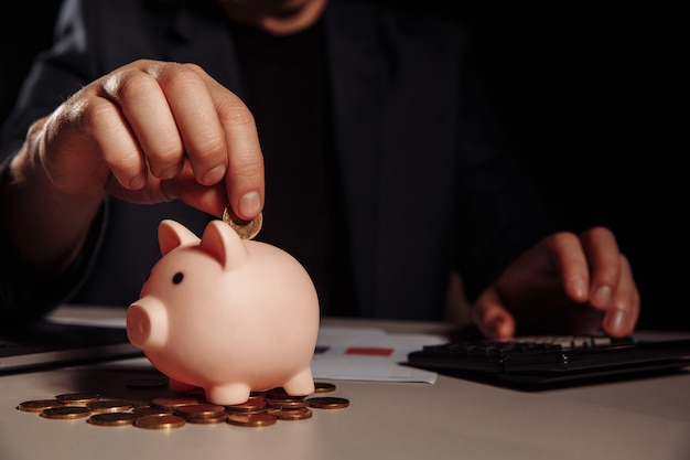 Businessman is counting profit on a calculator in office, piggy bank with coins at desk