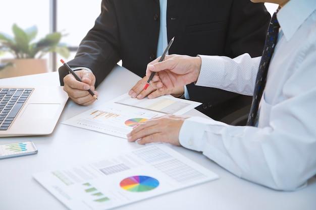 ビジネスマンは、ラップトップコンピューターのノートブックで投資収益率または投資リスク分析のための財務レポートを深く確認しています。
