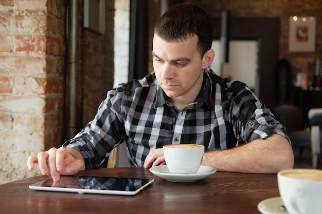 사업가 디지털 태블릿을 들고 카페에 앉아.