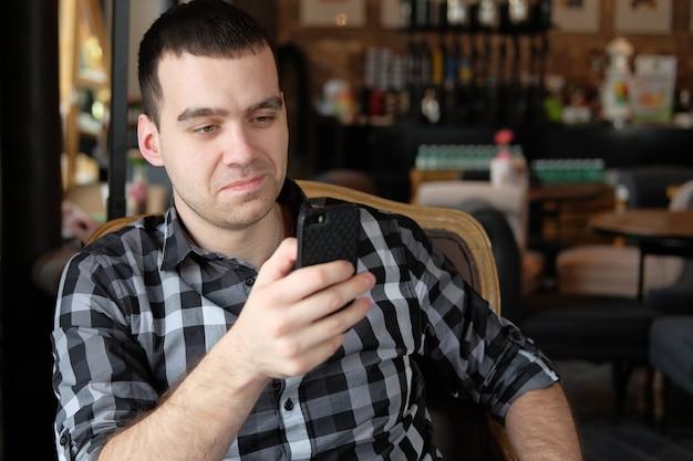 ビジネスマンはスマートフォンを持ってカフェに座っています。