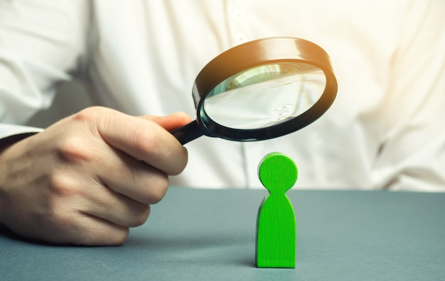 A businessman is holding a magnifying glass over a green man figure. search for a talented employee.