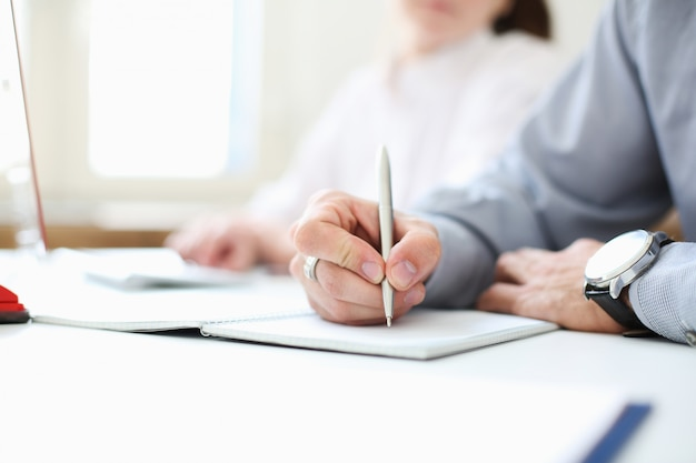 A businessman is holding a pen in his hand. put a signature. image with depth of field.