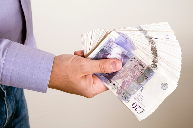 A businessman is holding a pound in his hand