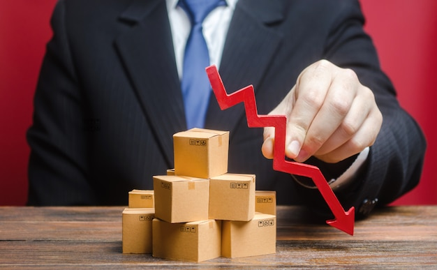 Businessman is holding a red arrow down above boxes stack pile. business industrial production drop.