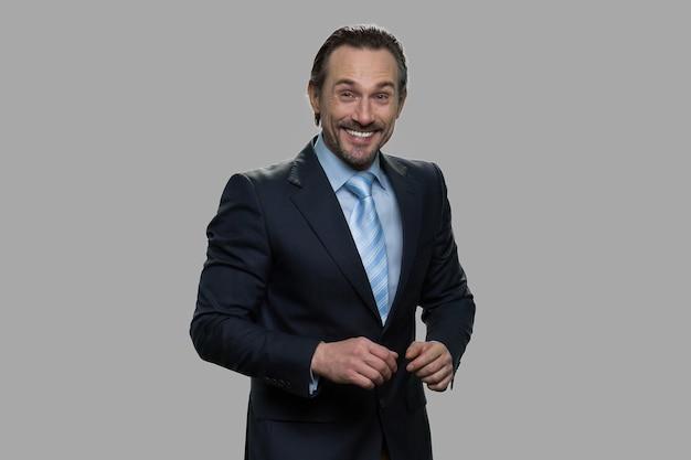 ビジネスマンは灰色の背景で笑っています。カメラを見て成功した笑顔の実業家。