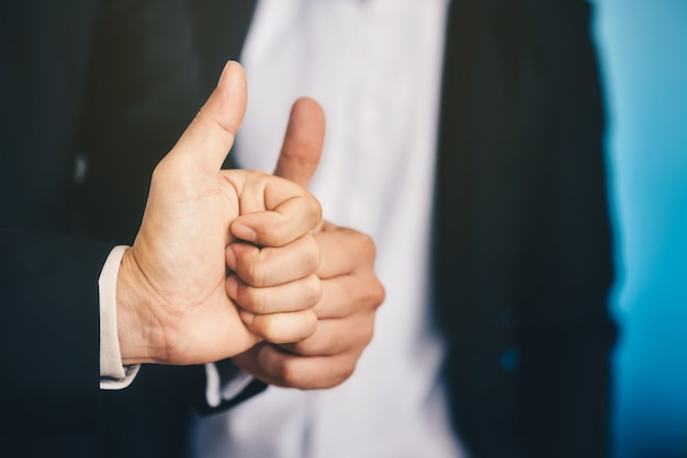 Businessman is lifting thumbs to display indescribably and agree to terms in business.