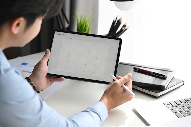Businessman is looking at calendar with daily agenda on tablet.