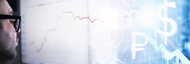 A businessman is looking at a graph on a monitor. an exchange broker evaluates stock market trends. a man with glasses in front of a curve of the dynamics of the economy.