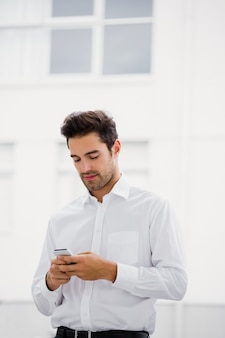 A businessman is looking his smartphone and texting