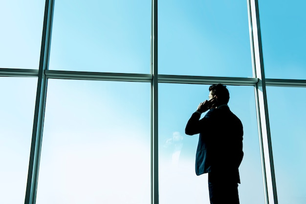 Businessman is looking out of a panoramic window.
