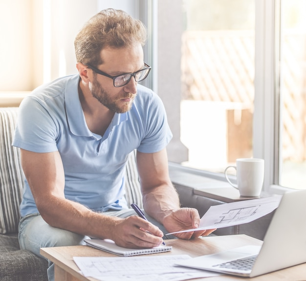 Businessman is making notes while sitting on couch at home.