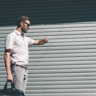 Бизнесмен по расписанию проверяет свои часы. пора сделать перерыв в работе. концепция тайм-менеджмента