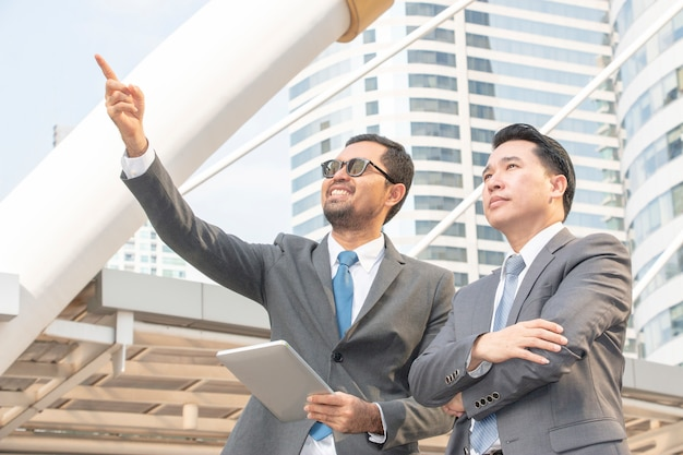 Businessman is pointing for his partner to see the project