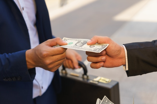 Businessman is receiving united states dollar banknote.