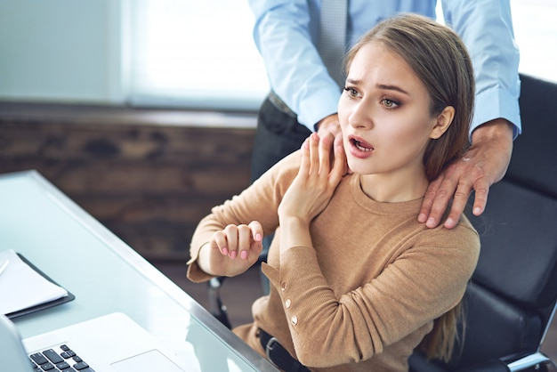 A businessman is sexually harassing female colleague by touching her shoulder