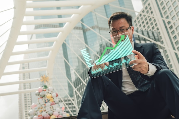 Businessman is showing a growing virtual hologram stock.