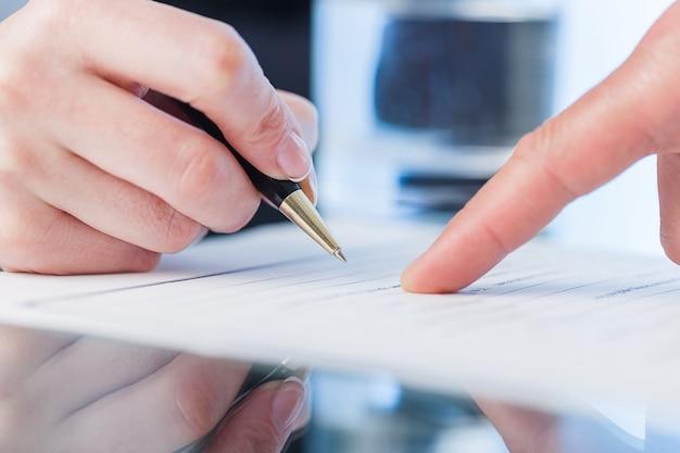 사업가가 계약, 비즈니스 및 법률 세부 사항에 서명하고 있습니다.