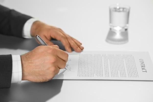 ビジネスマンは契約に署名しています。ボスは彼の署名を置きます。上司は決定する準備ができています。エグゼクティブは彼の動きをします。