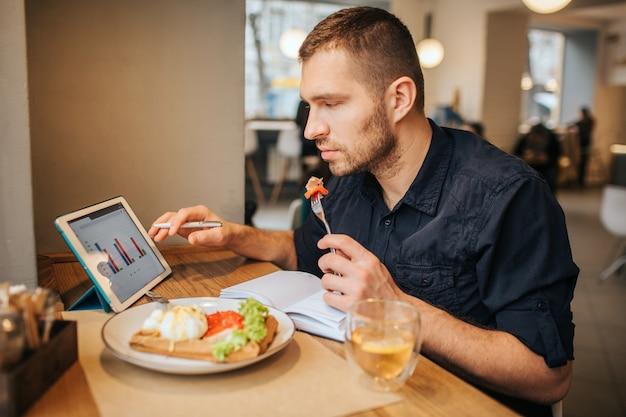 ビジネスマンはテーブルに座って、プレートから食事を食べています。彼はフォークの上にトマトを持っています。 guyは、画面にグラフィックが表示されたタブレットを見ています。彼は心配しています。