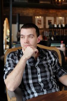 ビジネスマンはカフェに座っています。