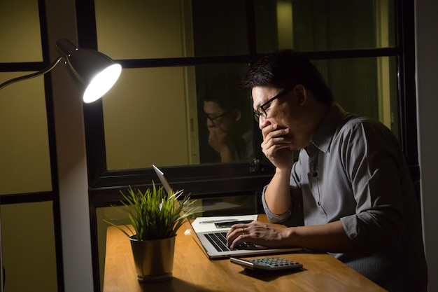 Businessman is sitting at a laptop in a dark office, working late concept