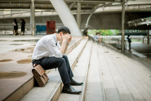 A businessman is sitting at the stairs with his handbag. he is failed in his job. he is serious, tired and upset. his work is not success. he has headache from his stress.