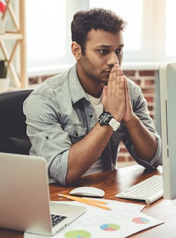 ビジネスマンは祈りのように設定された彼の手で座っています。