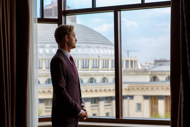 A businessman is standing and looking through the window to the cityscape