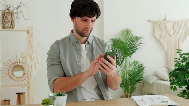 사업가 스마트 폰을 사용하고 사무실에서 작업하는 동안 웃고.