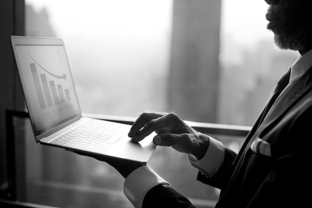 ビジネスマンはコンピューターのラップトップを使用しています