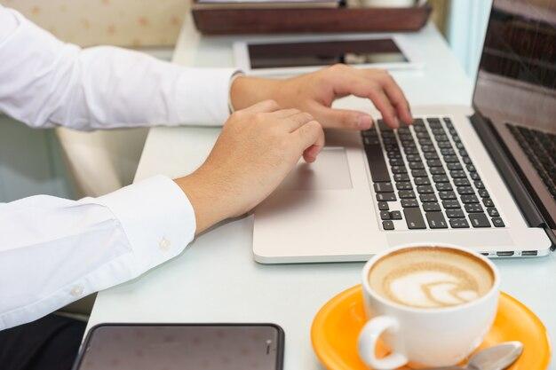 Businessman is using laptop on a desk.