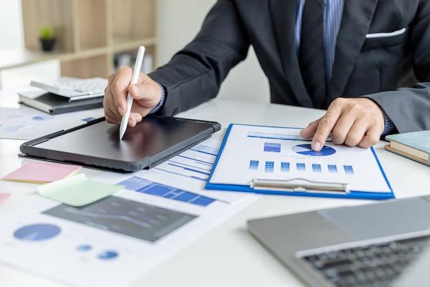 Бизнесмен использует планшет для сравнения информации о финансовых документах, он проверяет финансовые документы компании в офисе, финансовую отчетность компании. понятие финансового менеджмента.